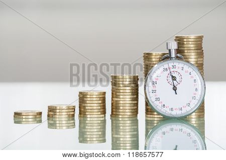 Stopwatch And Stacked Coins On Desk