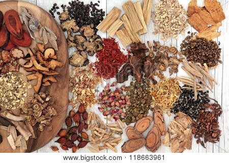 Traditional chinese herbal medicine ingredients on a maple wood board and loose over distressed white wood background.