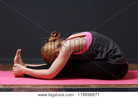 Young blonde woman doing yoga exercise