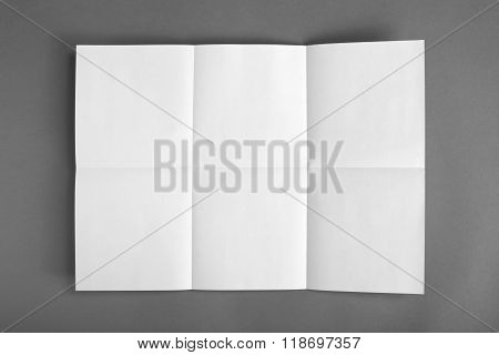 Close Up Of A Crumpled Unfolded Piece Of Paper On Gray Background.