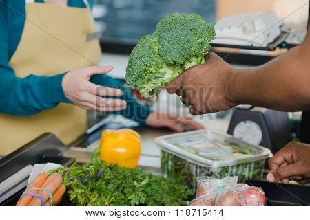 customer handing a sales assistant broccoli
