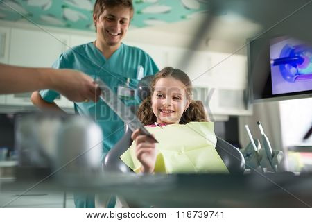 Little girl is having her teeth examined by dentist.Child not afraid of dentist