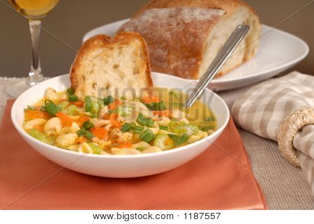 A Bowl Of Chicken Noodle Soup With Rustic Bread And A Glass Of W