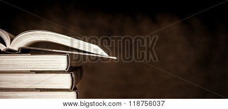 Stack of old books, with one open, over dark grunge background.
