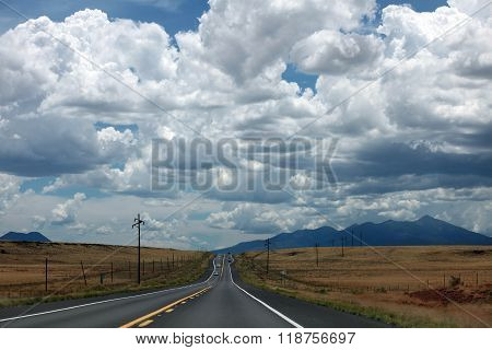 A desolate highway in western Utah winds through the desert under a dramatic sky. ** Note: Visible grain at 100%, best at smaller sizes