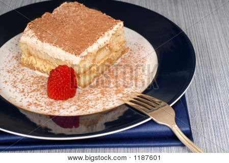 A Piece Of Tiramisu Dusted With Cocoa With A Fork On A Blue Plat