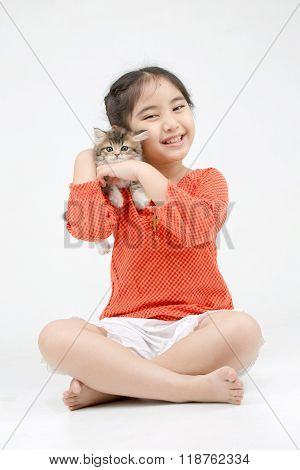 Little Asian girl hugging lovely Persian kitten