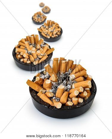 Curve ashtrays full of cigarette butts on a white background