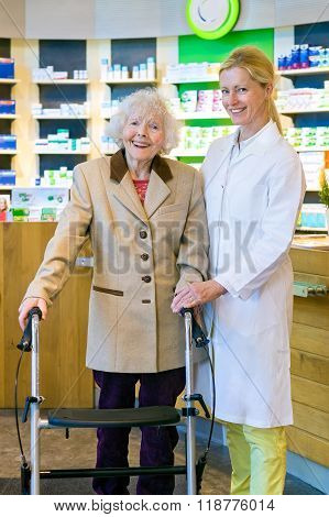 Joyful Pharmacist And Patient In Walker