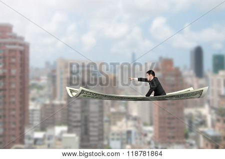 Businessman With Pointing Finger Gesture Sitting On Money Flying Carpet