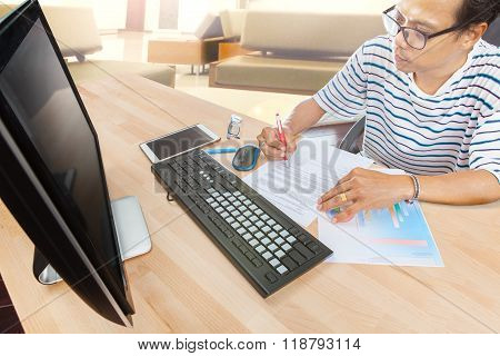 Man Working By Computer On Table At Home Living Room