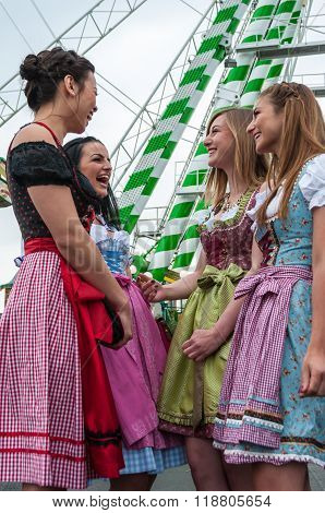 Attractive and joyful woman at German Oktoberfest with traditional dirndl dresses, big wheel in the