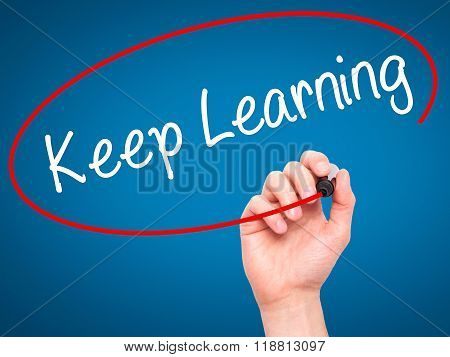 Man Hand Writing Keep Learning With Black Marker On Visual Screen