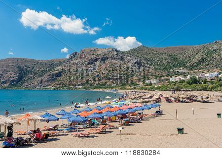 PALEOCHORA, CRETE, GREECE - AUGUST 2015: Sunbeds and tourist at sunny beach of Paleochora on Crete island.