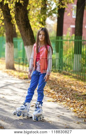 little young girl go on roller skates, outdoor, in the evening summer