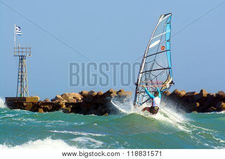 Windsurfer making extreme tricks on a flat water at Santorini island