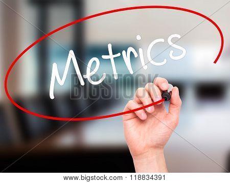 Man Hand Writing  Metrics  With Black Marker On Visual Screen
