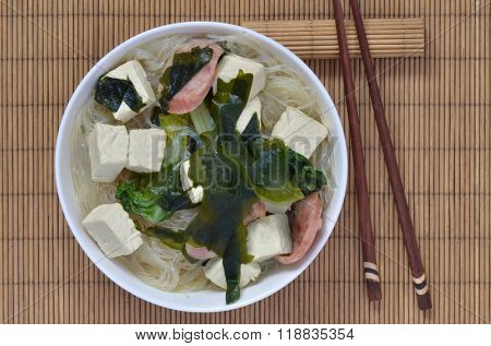 Chinese dish with tofu, seaweed, pork, green vegetables and rice pasta.