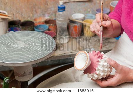 A pottery decorator painting a typical ceramic pine cone in his work table in Caltagirone Sicily poster