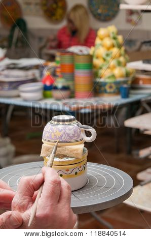 A pottery decorator finishing a ceramic small cup with floral motifs in his work table in Caltagirone Sicily poster