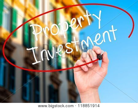 Man Hand Writing Property Investment With Black Marker On Visual Screen