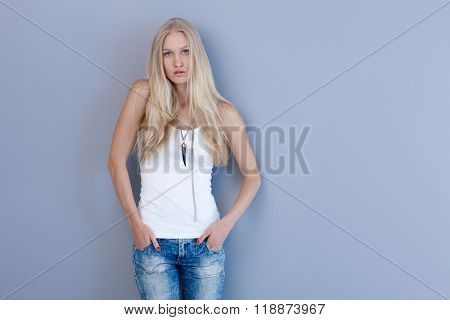 Attractive blonde casual woman standing by blue wall with hands in pockets.