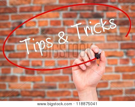 Man Hand Writing Tips & Tricks With Black Marker On Visual Screen