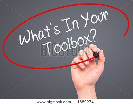 Man Hand Writing  What's In Your Toolbox? With Black Marker On Visual Screen