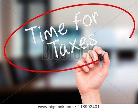 Man Hand Writing Time For Taxes With Marker On Transparent Wipe Board