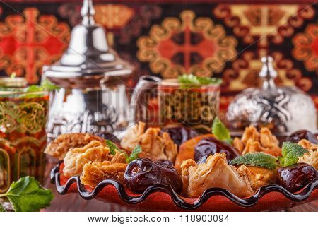 Moroccan Mint Tea In The Traditional Glasses With Sweets.