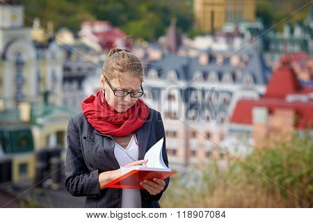 Beautiful serious woman in jacket and glasses reads red book against summer buildings