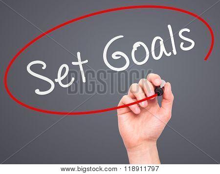 Man Hand Writing Set Goals On Visual Screen