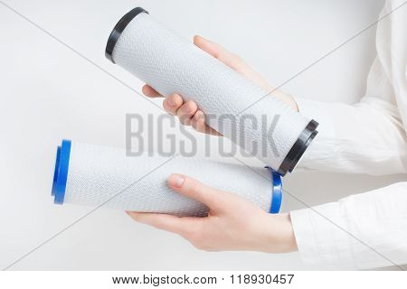 two water filter cartridges in human hands