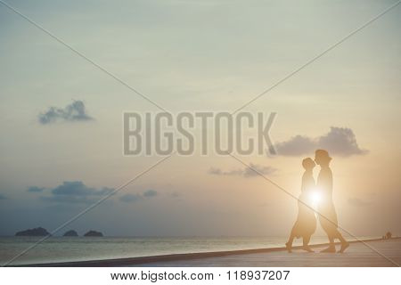 Kissing Couple In Aladdin Trousers On The Tropical Sunset Background.