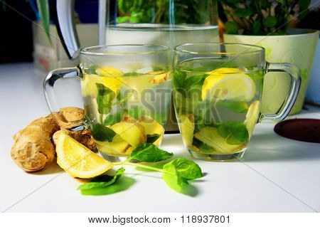 Two teacups with fresh peppermint ginger and lemon on the table