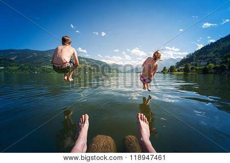 girl and boy jumping in lake water at summer holiday