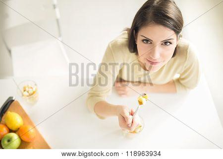 Healthy looking cheerful woman eating homemade organic fruit mix salad