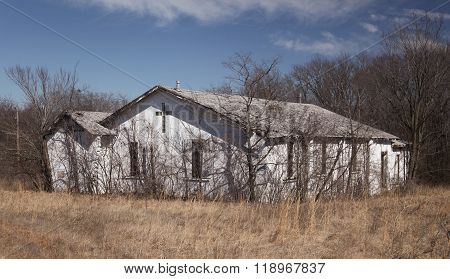 A Wider View of an Old Church Sitting Among Weeds in Rural Oklahoma