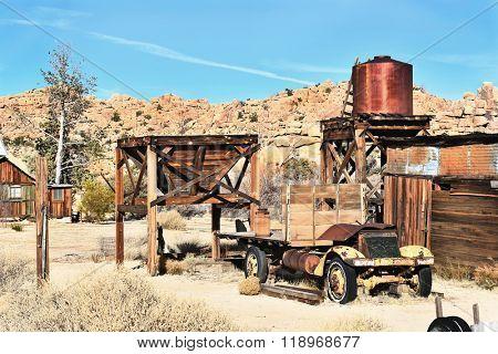JOSHUA TREE, CALIFORNIA - JANUARY 1, 2016: Truck and Water Tower. A rusted old truck and water tower at Keys Ranch in Joshua Tree National Park.