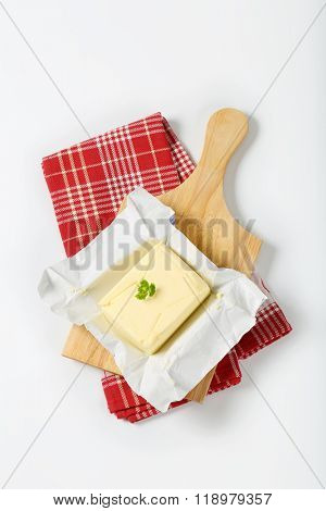 block of fresh butter on wooden cutting board