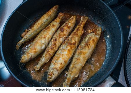 Fried small smelt tasty fish on a barbecue  hotplate