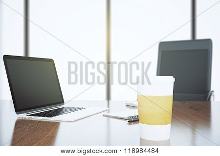 Wooden Office Table With Blank Laptop Screen And Paper Coffee Cup With Chiar And Big Window Backgrou