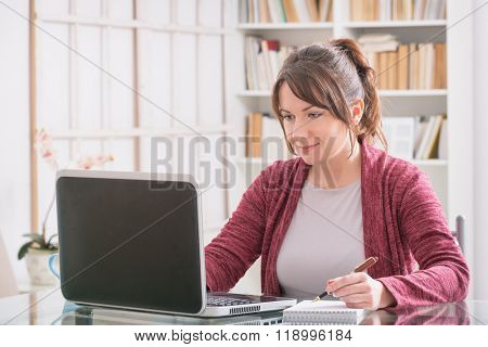 Mid age woman sitting at table and working with laptop