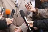 Interview with microphones held in front of spokesman or politician poster