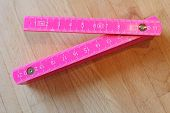 pink foldable ruler on a wooden background poster