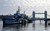 The retired battleship HMS Belfast in from of Tower Bridge in London England UK poster