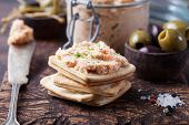 Smoked salmon and soft cheese spread, mousse, pate in a jar with crackers, olives and capers on a wooden background poster