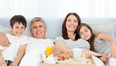 Family having breakfast in their bed at home poster