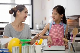 Little Asian cute chef cooking a bakery in kitchen with mother