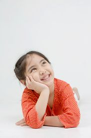 Little Asian girl lying and thinking